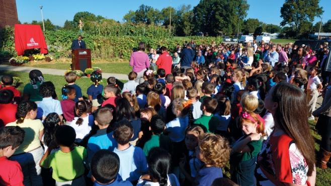 school children outside in garden listen to man at podium